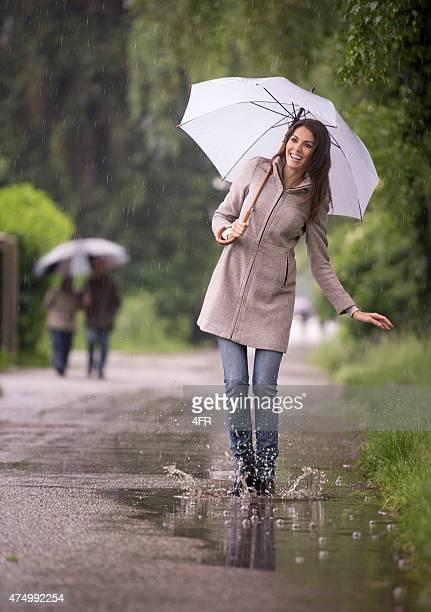 Beautiful Woman dancing in the Rain with Umbrella, Puddle Fun
