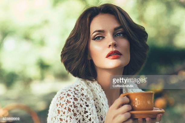 Belle femme boire le thé dans un magnifique parc