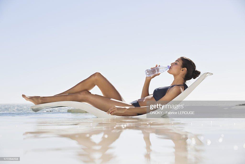 Beautiful woman drinking water on the beach : ストックフォト