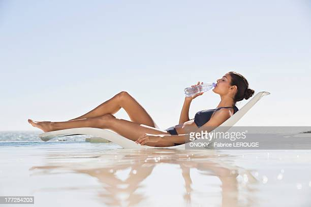 Beautiful woman drinking water on the beach