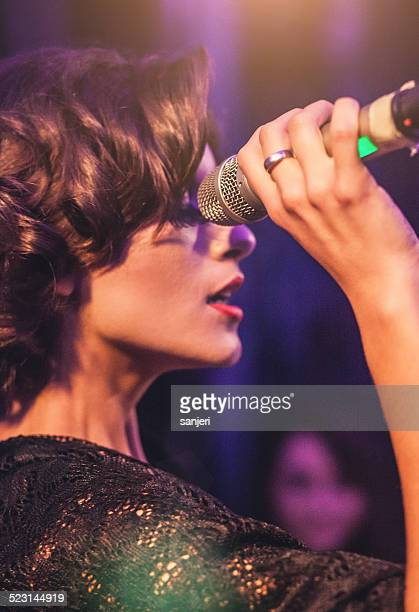 Beautiful woman during concert holding a microphone
