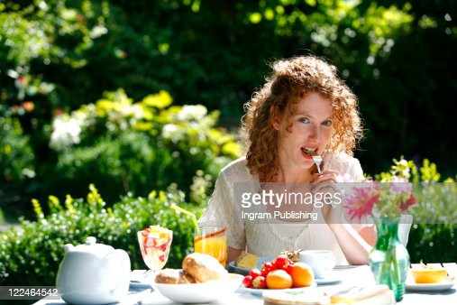A beautiful woman eating a meal in her garden : Stock-Foto