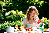 A beautiful woman eating a meal in her garden