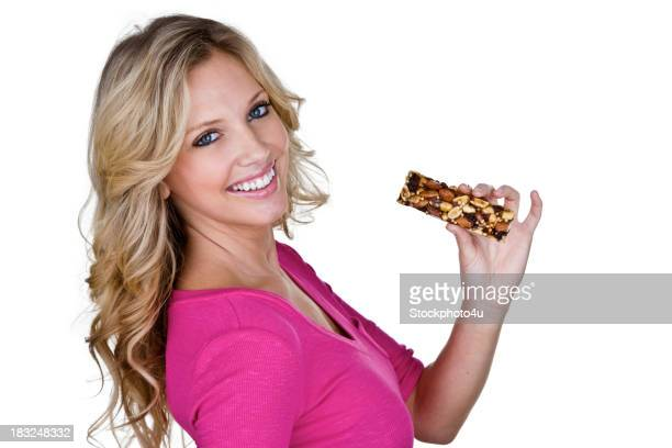 Beautiful woman eating a nut health bar