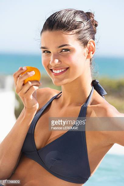 Beautiful woman eating a tomato on the beach