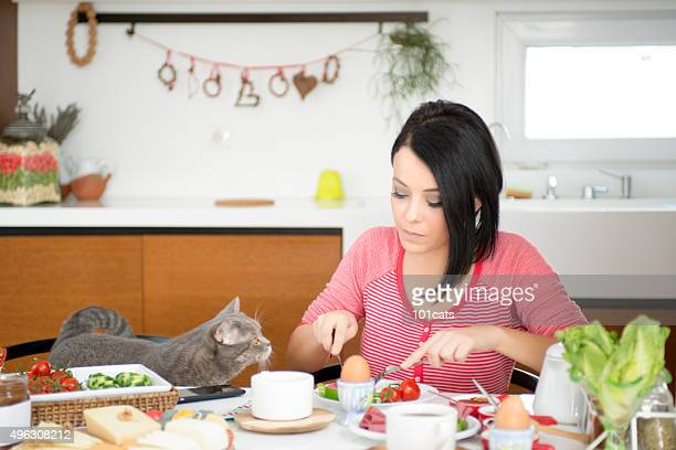 beautiful woman eating breakfast with cats