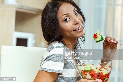 Beautiful woman eating fresh salad in modern kitchen : Stock Photo
