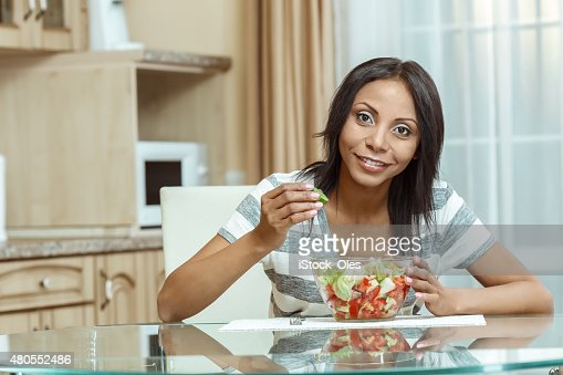 Beautiful woman eating fresh salad in modern kitchen : Stock Photo
