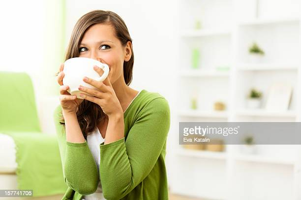Schöne Frau genießen eine Tasse Kaffee wie zu Hause fühlen