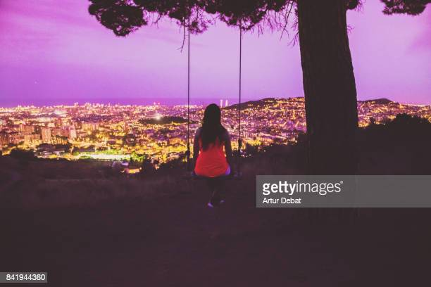 Beautiful woman enjoying a unique swing on a tree on top of Barcelona mountain contemplating the city at night with elevated point of view during summer good vibes in a romantic place.