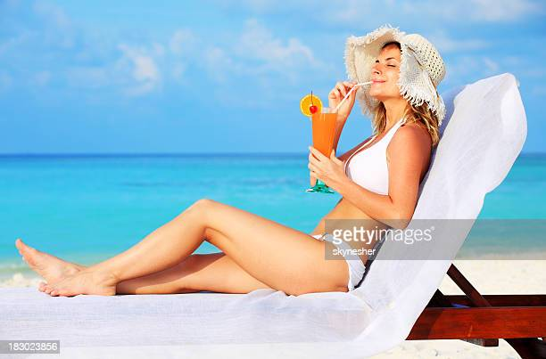 Beautiful woman enjoying at the sun and drink cocktail.