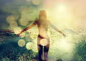 Beautiful Woman Standing in the Sea Waves and Enjoying Sunshine with Open Arms. Double Exposure Filtered Photo with Bokeh.