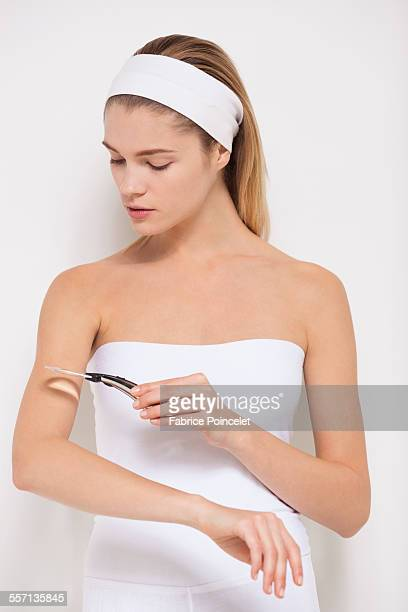 Beautiful woman examining her skin with magnifying glass