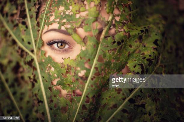 Beautiful woman eye through the leaf in nature