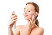 Beautiful woman face spray on face lotion cosmetology on white background isolation