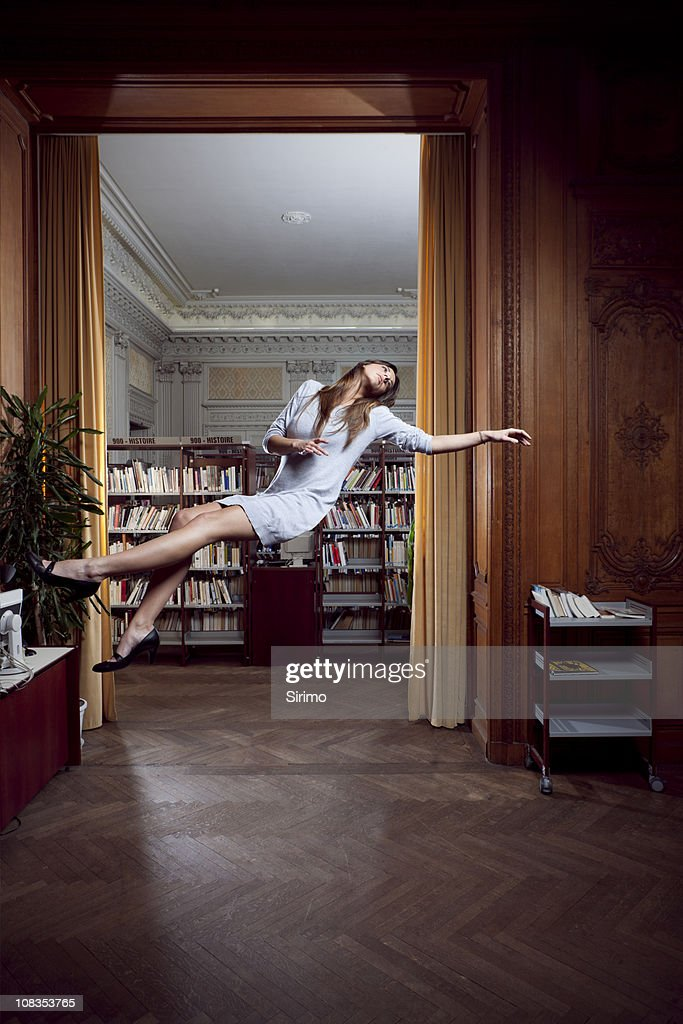 Beautiful woman floating in library concept