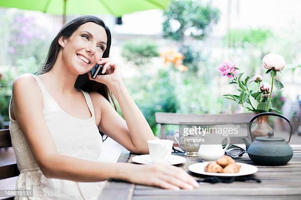 Schöne Frau, die Ihr Frühstück auf der Terrasse mit Handy.