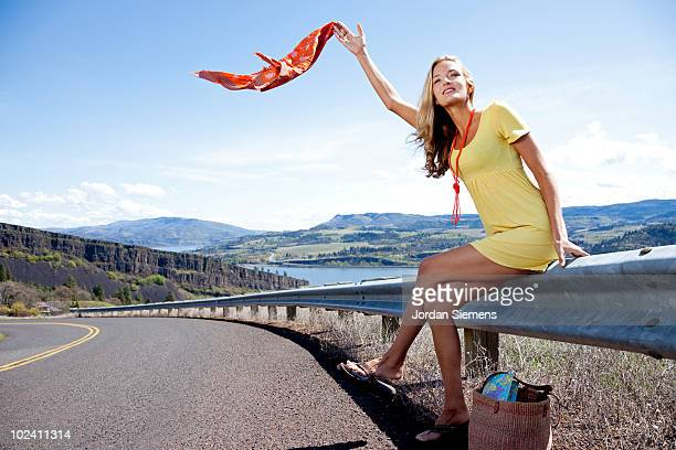 A beautiful woman hitch hiking on the side