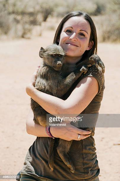 Beautiful woman holding a baby baboon in Namibia, Southern Africa