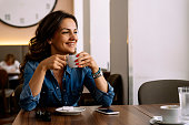 Beautiful woman holding a cup of coffee in coffee shop.