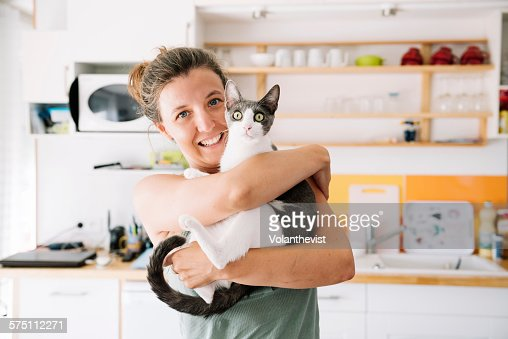 Beautiful woman holding a cute cat at home