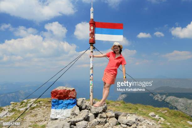 Beautiful woman holding a flag on top of Maglic peak