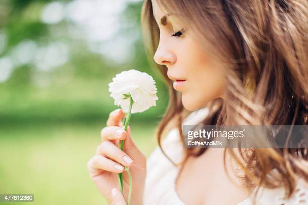 Beautiful woman holding a flower in her hand