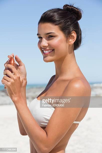 Beautiful woman holding a suntan lotion on the beach