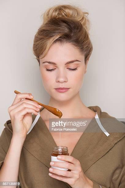 Beautiful woman holding honey jar