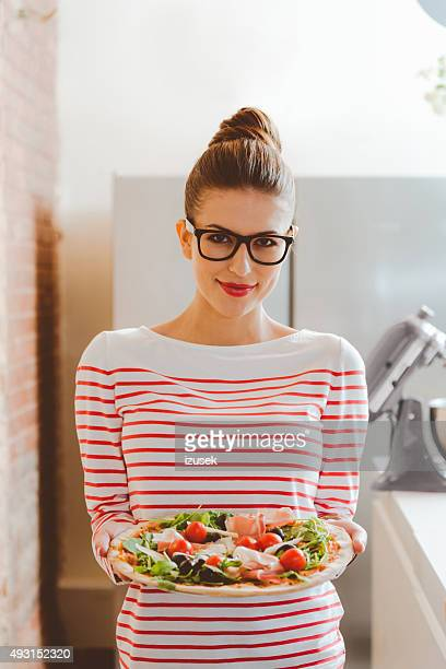 Beautiful woman holding pizza in hands, smiling at camera