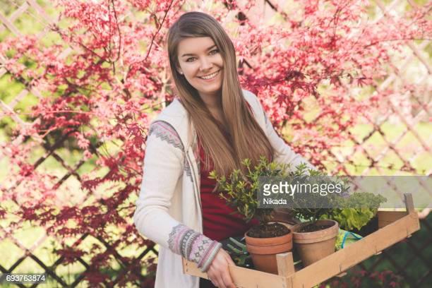 schöne Frau mit Pflanzen in einem Garten