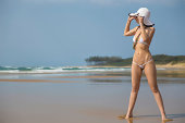 Beautiful woman standing on the beach in a small white bikini