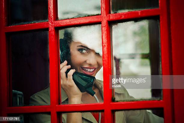 Beautiful woman in a red telephone booth