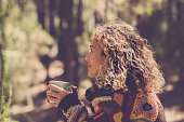 Beautiful woman in autumn forest enjoying the feeling with the nature with a warm sweater - lady sits with trees in background in a forest and holds a cup with a hot drink in her hands. Girl travel an
