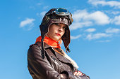 beautiful woman in aviator helmet on the sky background outdoors