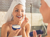 Beautiful young woman in bath towel is applying cream on her face and smiling while looking into the mirror in bathroom