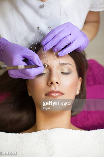 Beautiful woman in beauty slon on eyebrow makeup treatment