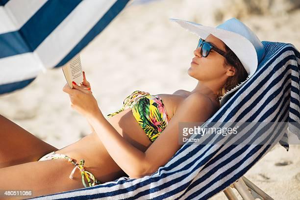 Beautiful woman in bikini at beach reading book and sunbathing