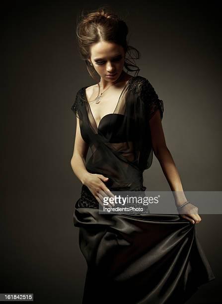 Schöne Frau im schwarzen Kleid auf dunklem Hintergrund