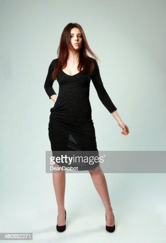 Hermosa mujer en vestido negro de pie : Foto de stock