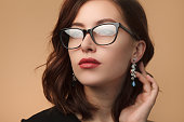 Beautiful brunette woman wearing black rimmed spectacles touching drop earrings looking away.
