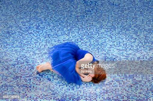 beautiful woman in blue dress lying in a pool