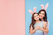 beautiful woman in bunny ears hugging child and smiling at camera on blue and pink background
