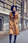 Young beautiful brunette walking and enjoying old city. She is wearing brown coat because is cold and her hands are in pocket. On head she has nice stylish black hat. As an addition she has black hand