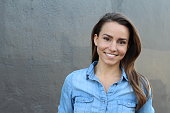 Beautiful woman in a blue casual denim shirt smiling - Stock image with copy space for text.