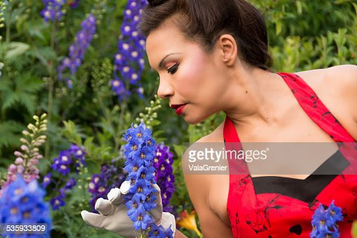 Beautiful woman in garden, head turned to sniff delphiniums. : Stock Photo