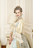 Beautiful woman in historical dress in Baroque style in the interior