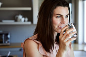 Beautiful woman drinking water and smiling in kitchen