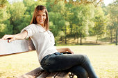 Beautiful young woman sitting on the bench and smiling in city park at summer day