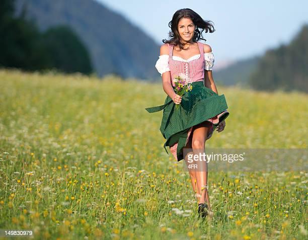 Schöne Frau in Oktoberfest Dirndl Mode, die durch die Meadows